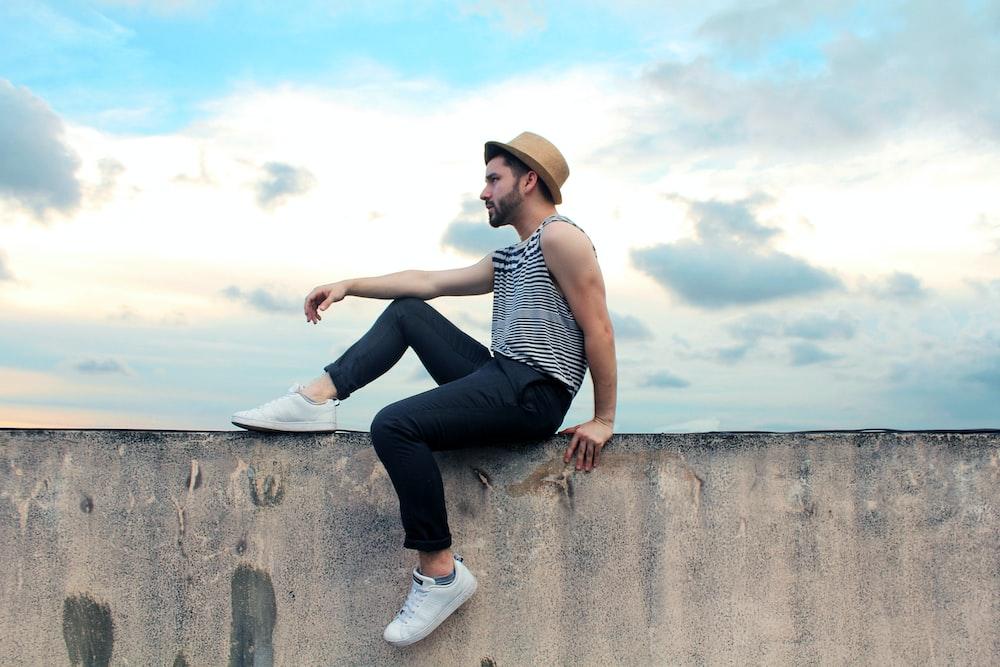 man sitting on concrete pavement