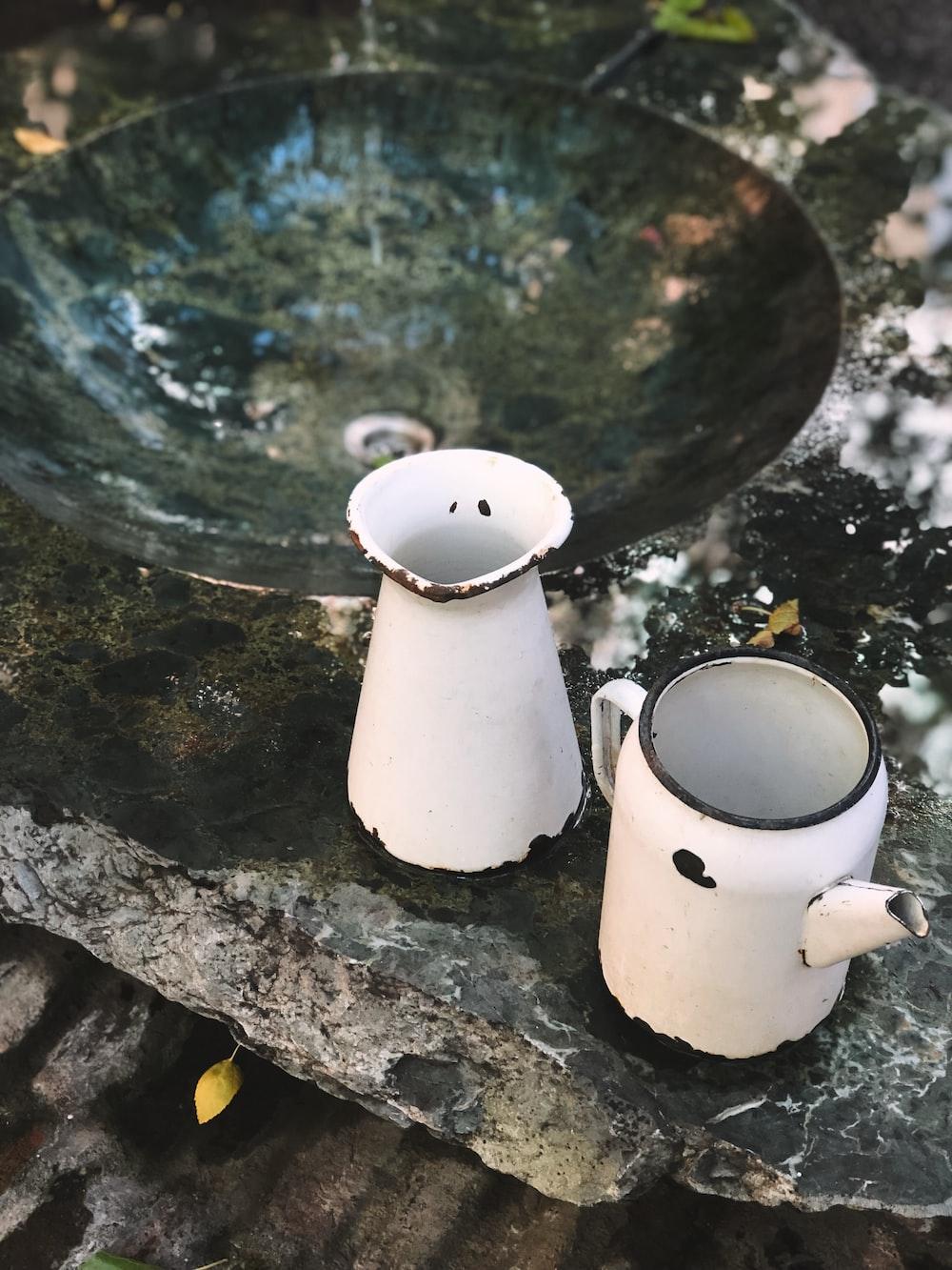 two white enamel pitchers beside a sink