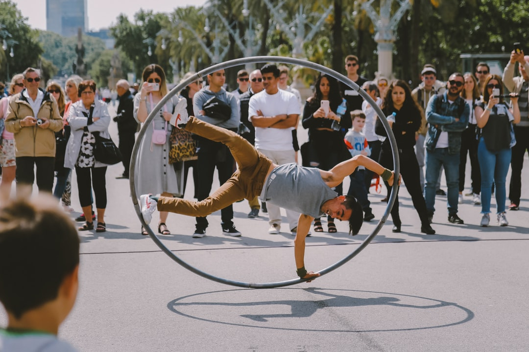 A street artist performing a stunt with a giant hula hoop in front of a crowd