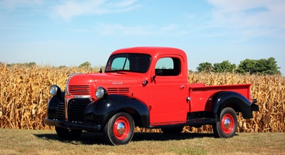 red and black single cab pickup truck beside a corn field ohio teams background