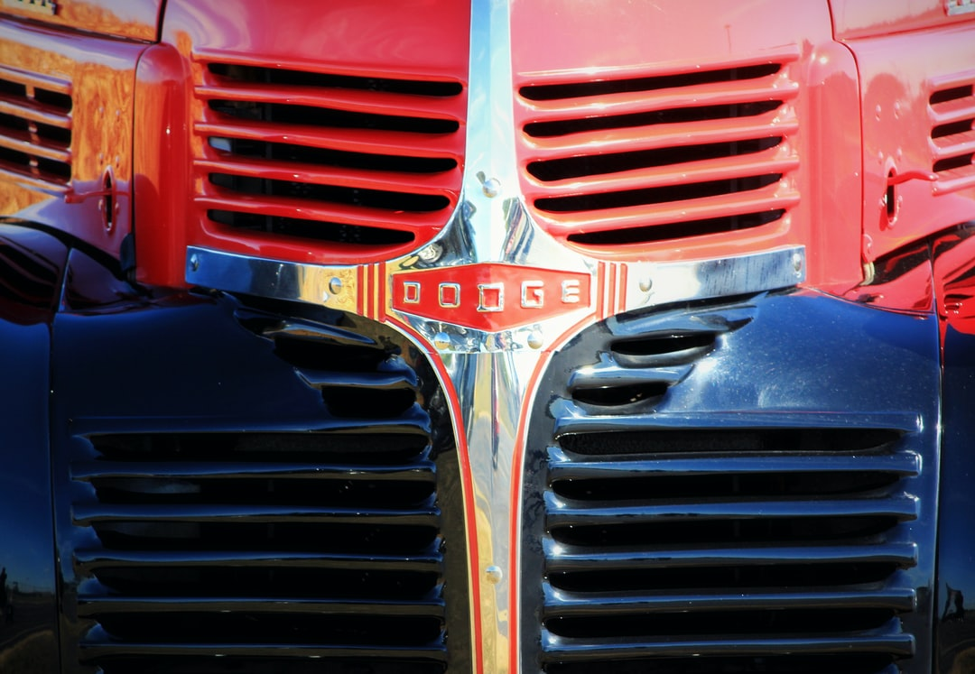 The grille of a red, vintage Dodge pickup truck sitting in front of a cornfield in the country.
