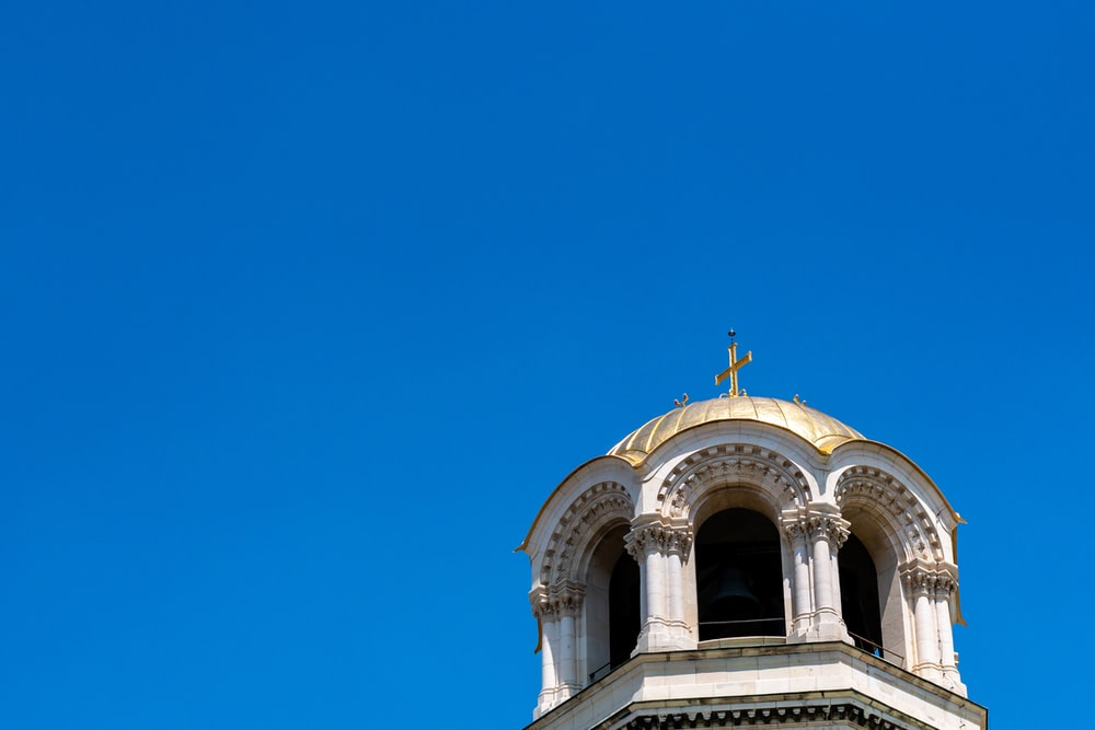 low-angle photography of white and gold dome cathedral under a calm blue sky