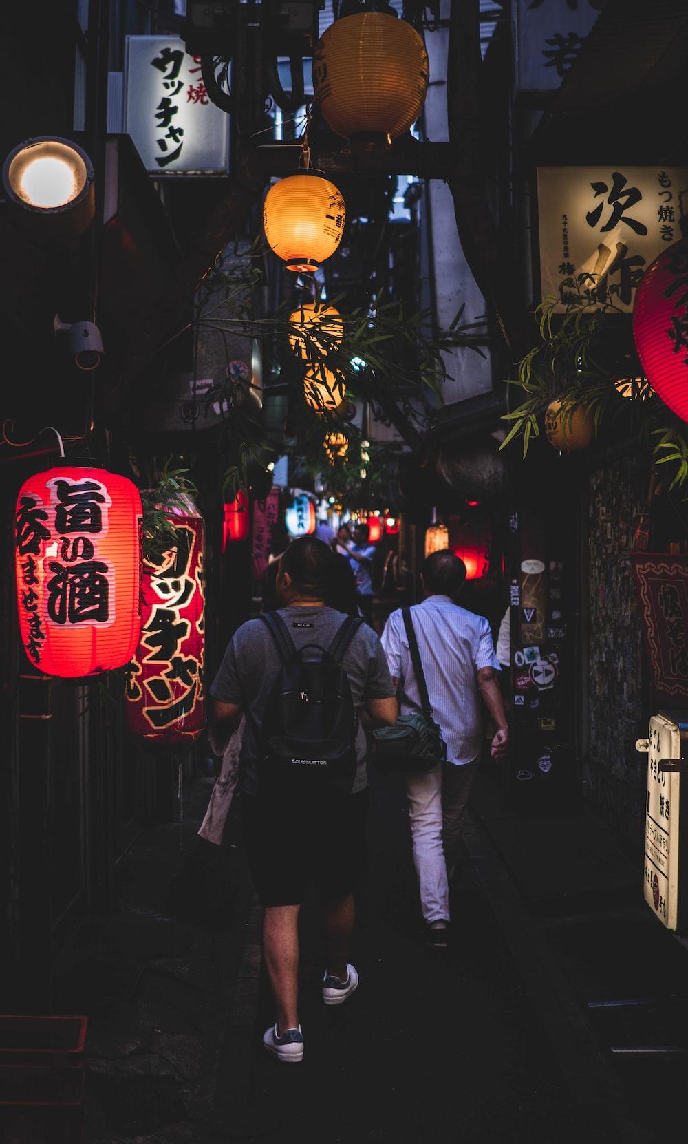 men walking along narrow street with hanging lanterns