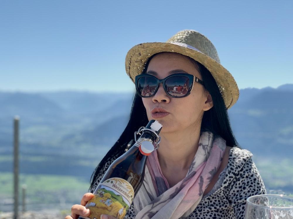 woman holding glass bottle