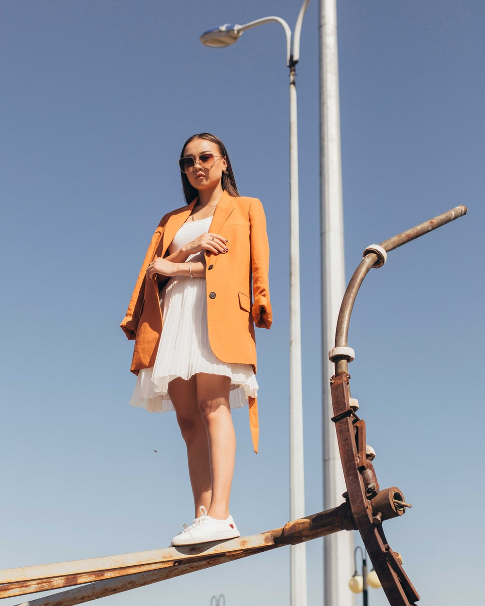 woman in sunglasses wearing orange coat