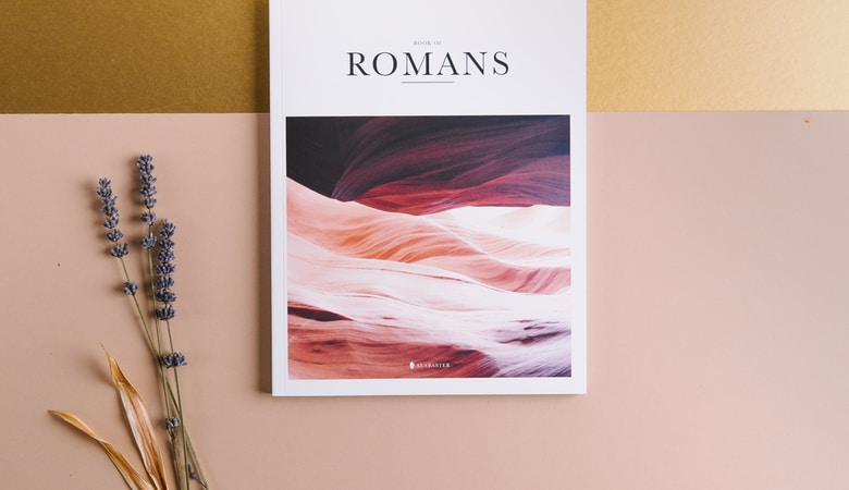 Romans book beside lavender flowers