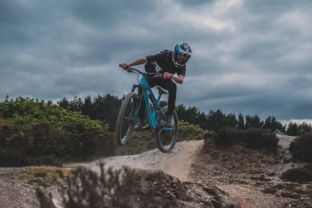 man wearing black pants riding hardtail mountain bike