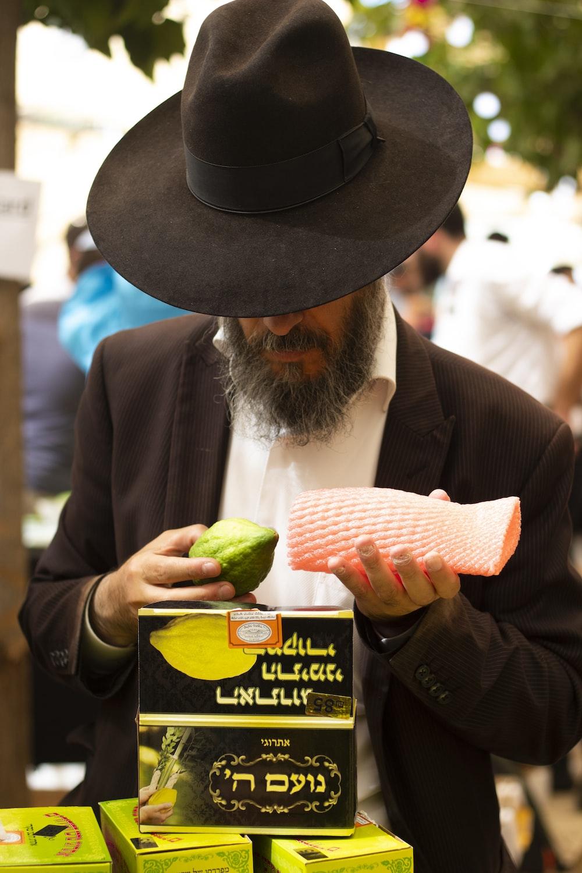 man wearing black hat holding green fruit