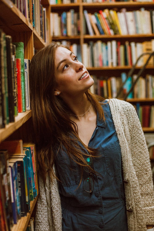 woman in cardigan leaning on bookshelf
