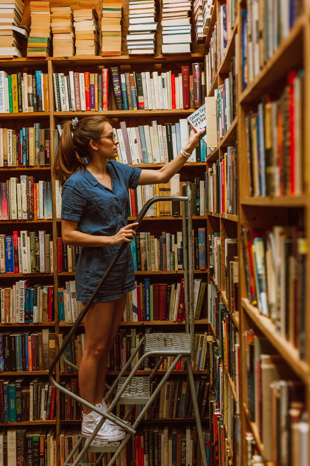 woman steps on ladder while holding book