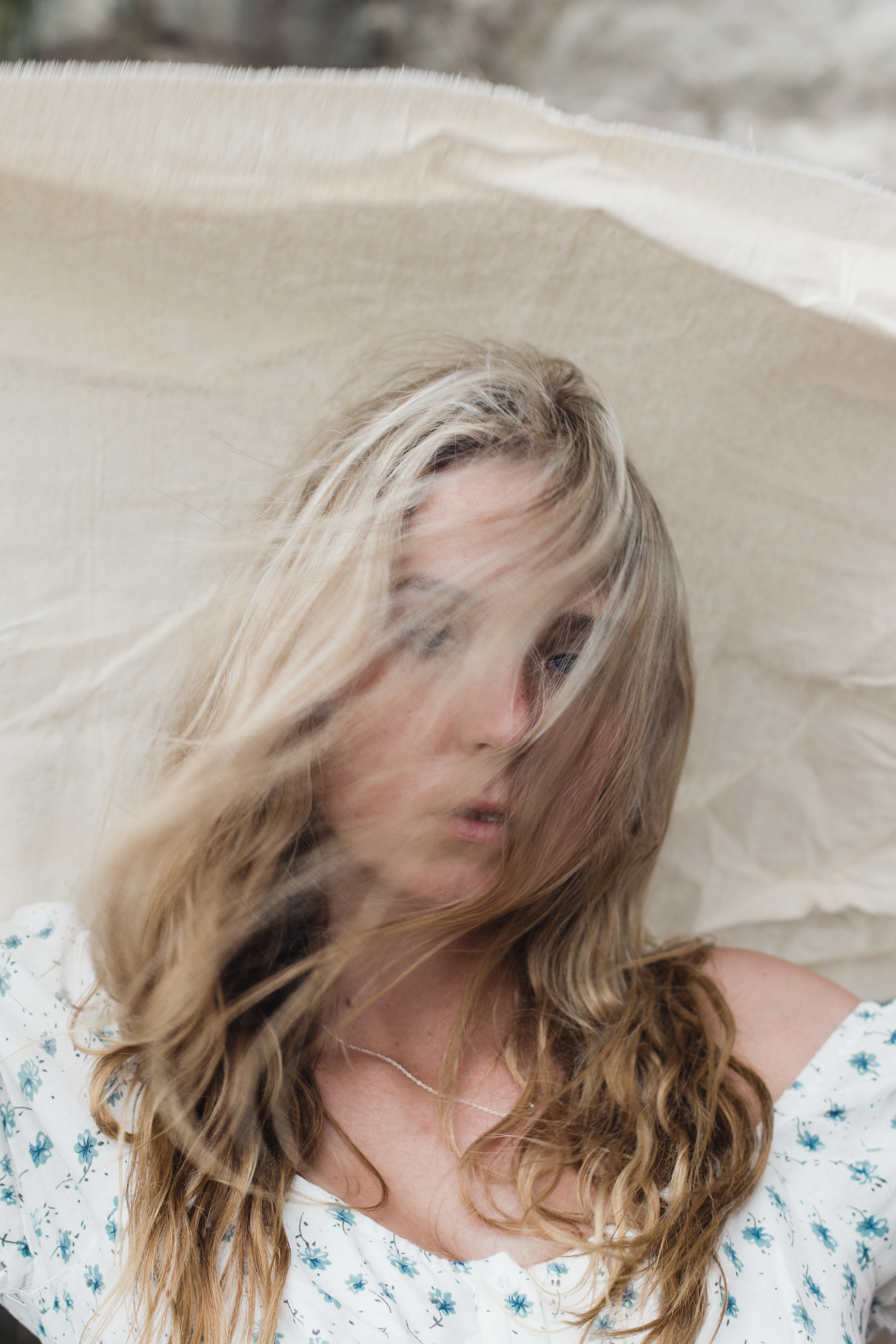 Wind and hair in face, holding fabric in the wind