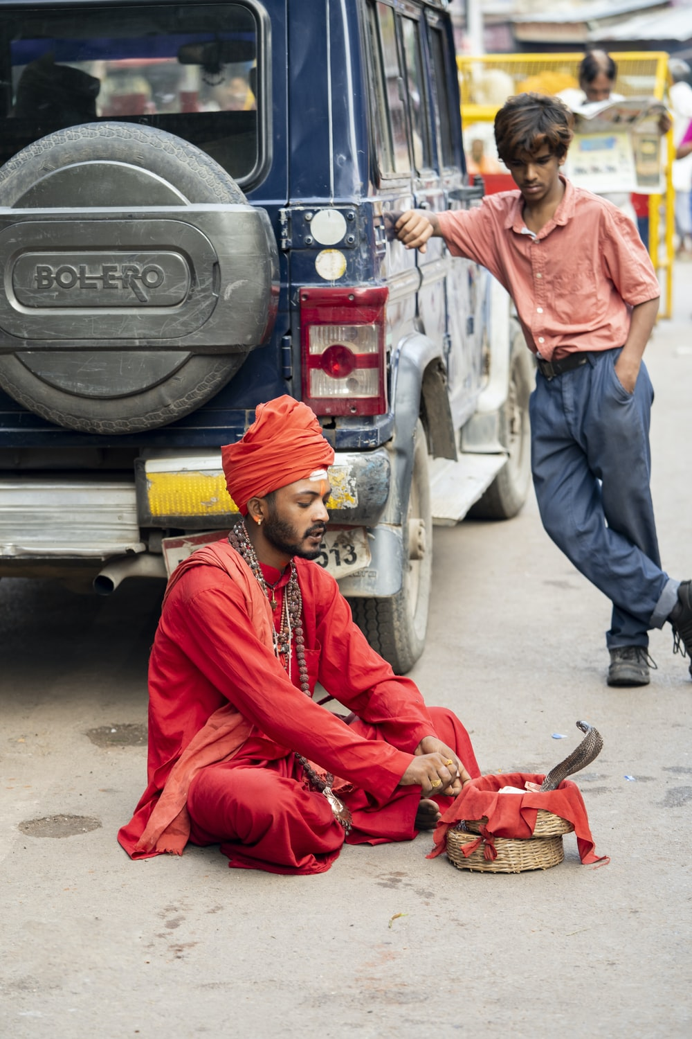 man wearing red thobe robe sitting and playing with snake and another man standing and touching blue vehicle while watching man performing