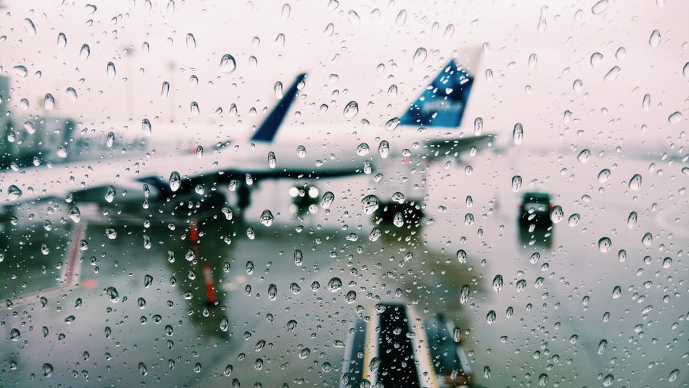 water drops viewing white and blue airplane
