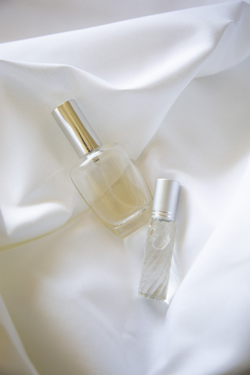 two bottles on white textile