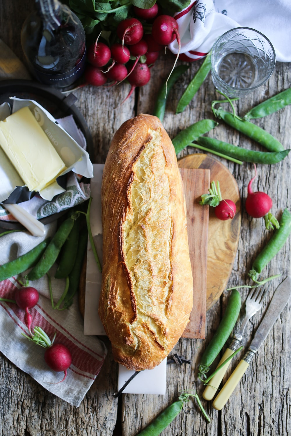 bread on cutting board surrounded with vegetables