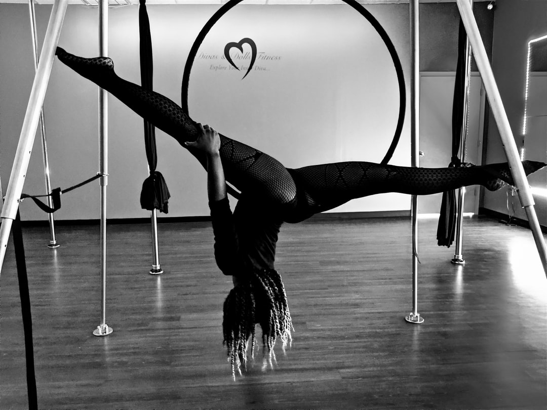 Black and White photo of a female Dancer using fabric to balance herself in a studio with wood floors.