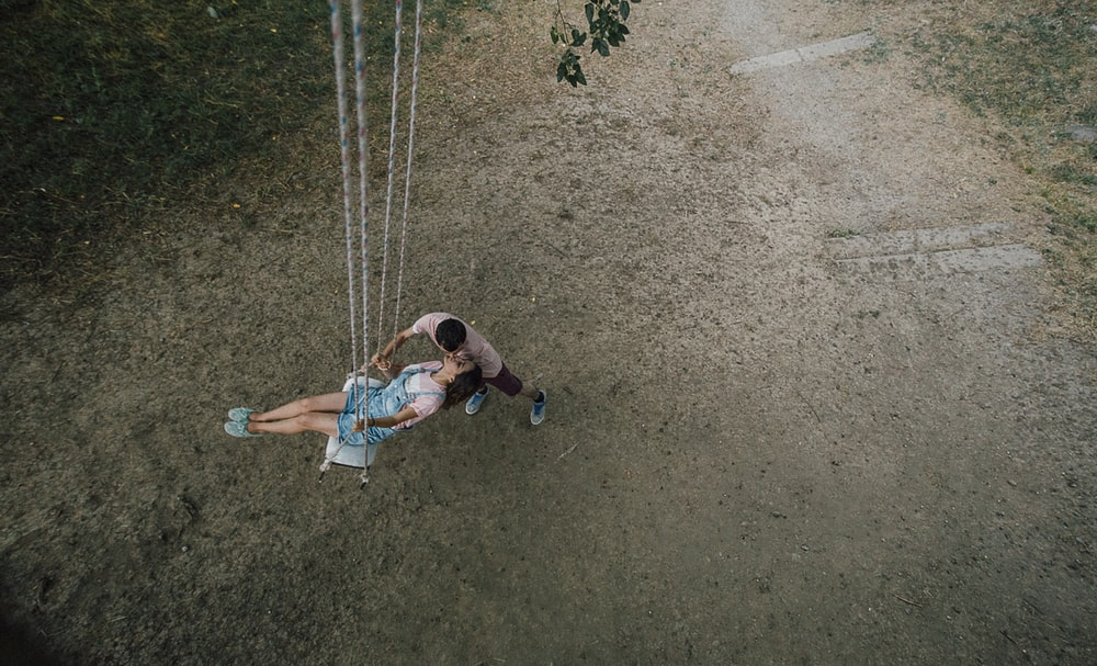 woman riding on swing beside man close-up photography