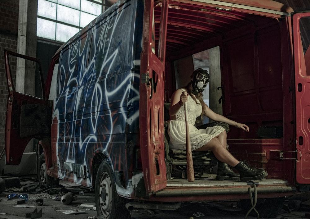 woman sitting in van while holding baseball bat