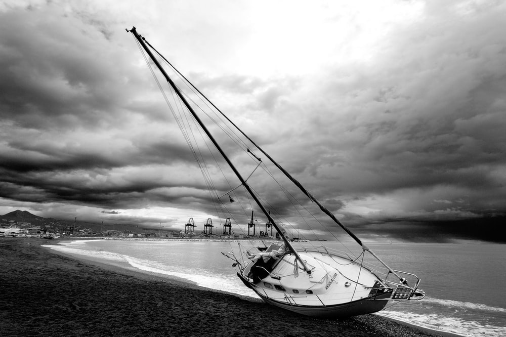 grayscale photography of sailboat on seashore