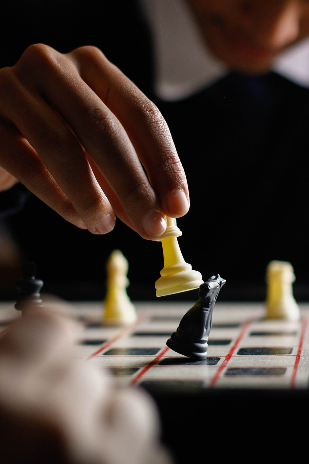 person holding white chess piece