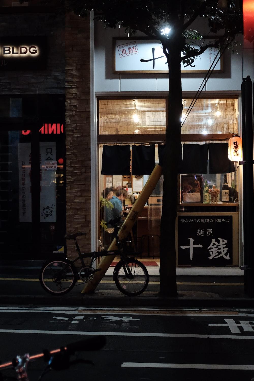 black bicycle parked beside sidewalk