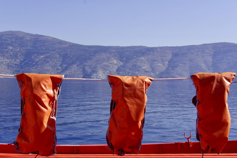 three red leather bags hanging on rope