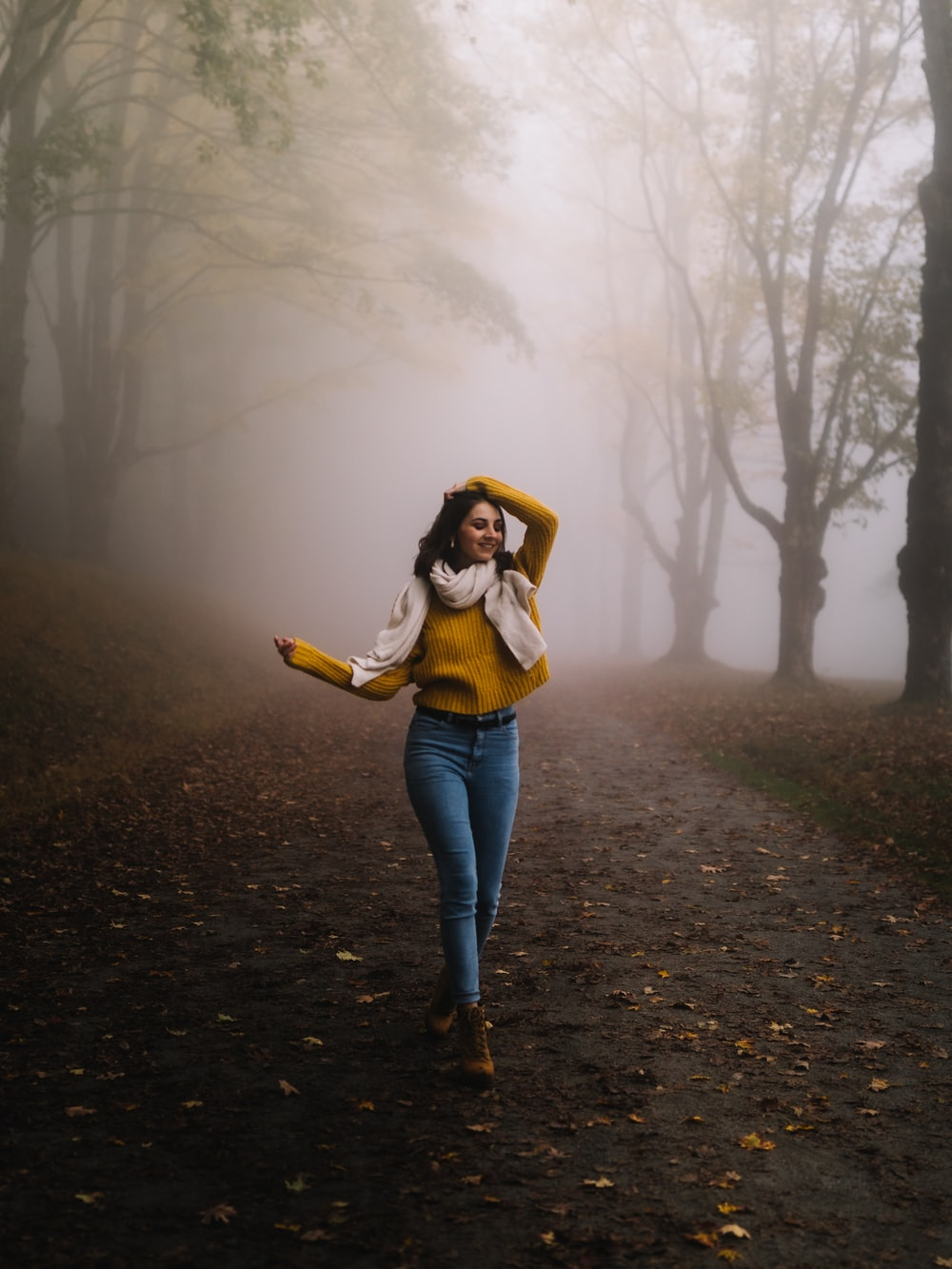 woman walking on road near trees during day
