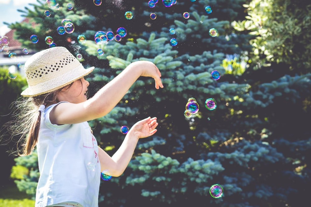 girl playing bubbles near green leaf plant