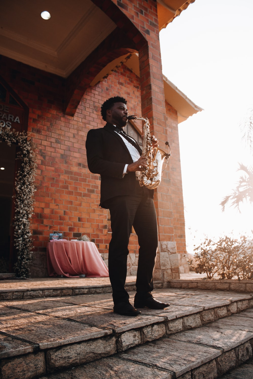 man playing saxophone during daytime
