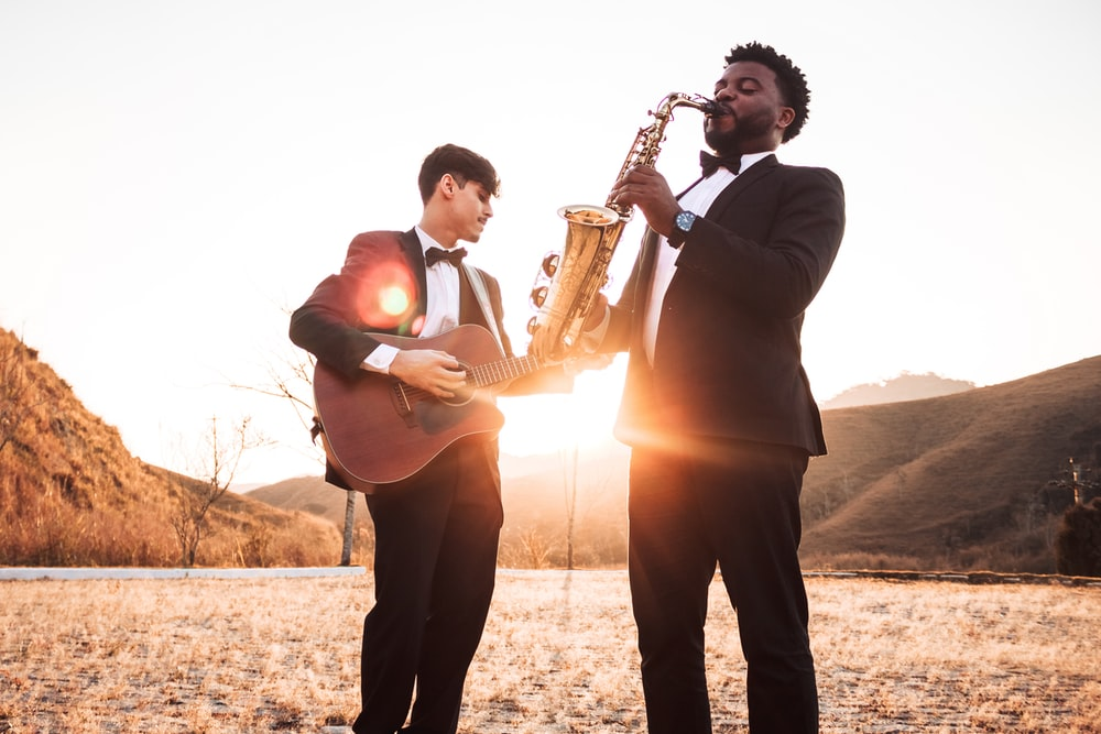 two men playing saxophone and guitar