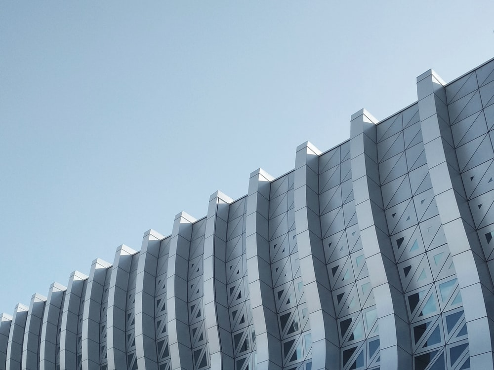 architectural photography of a gray concrete building under a clear sky