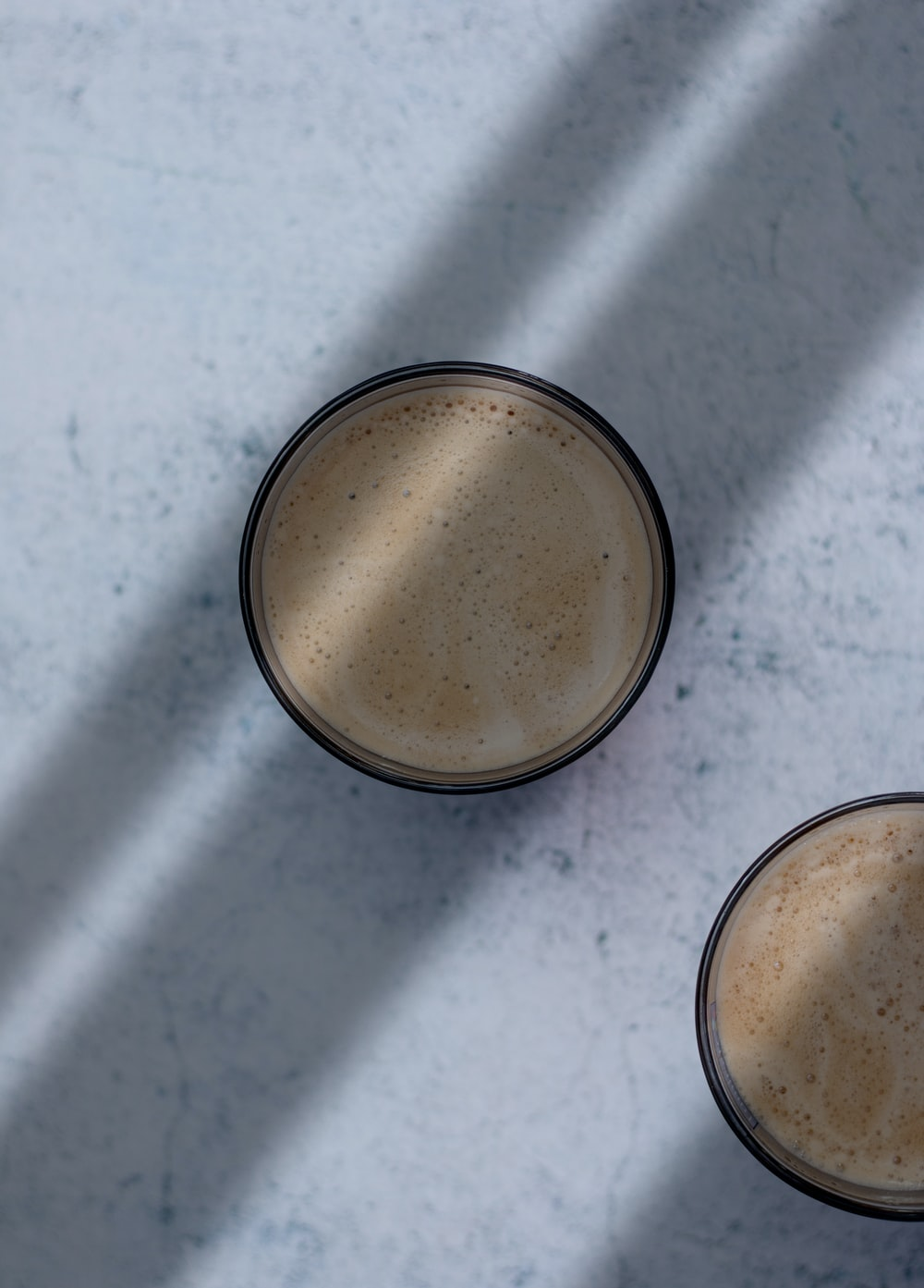 two black ceramic cups with cappuccino