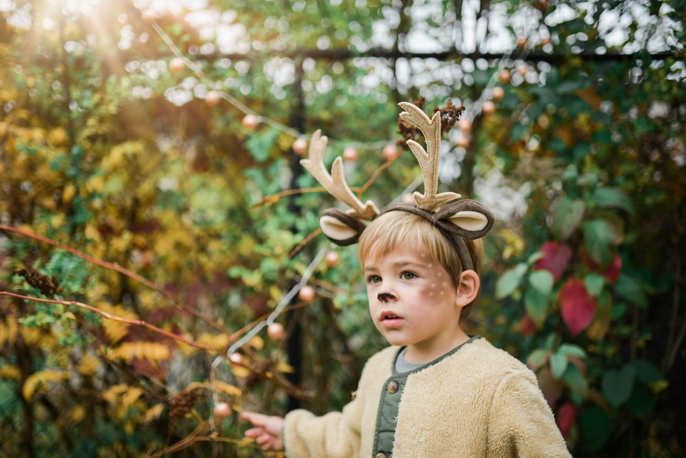 boy wearing deer head band near plants