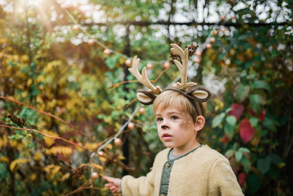 boy wearing deer head band near plants