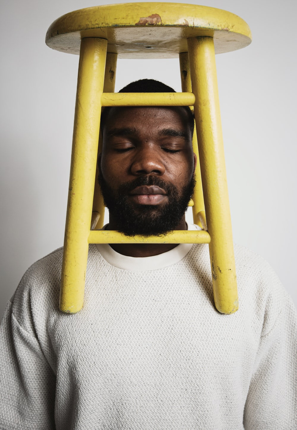 yellow wooden stool on man's shoulder
