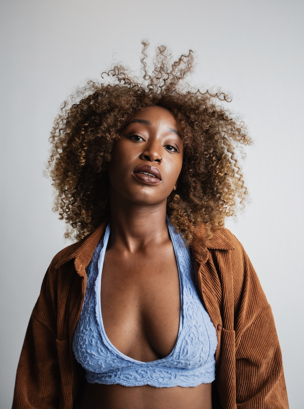 woman wearing blue lace bralette and brown corduroy cardigan