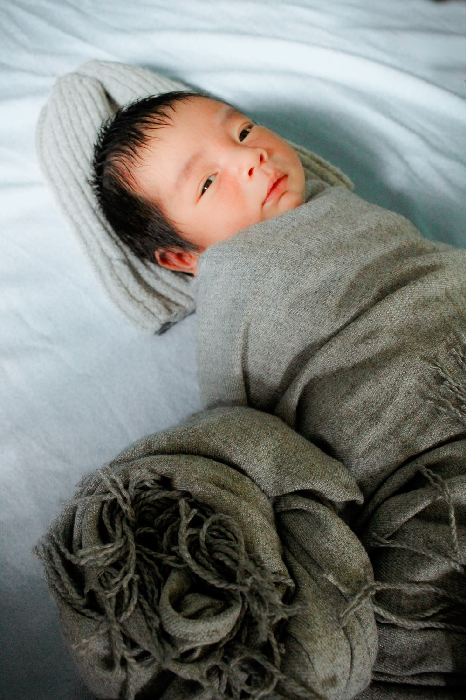 baby in gtey blanket