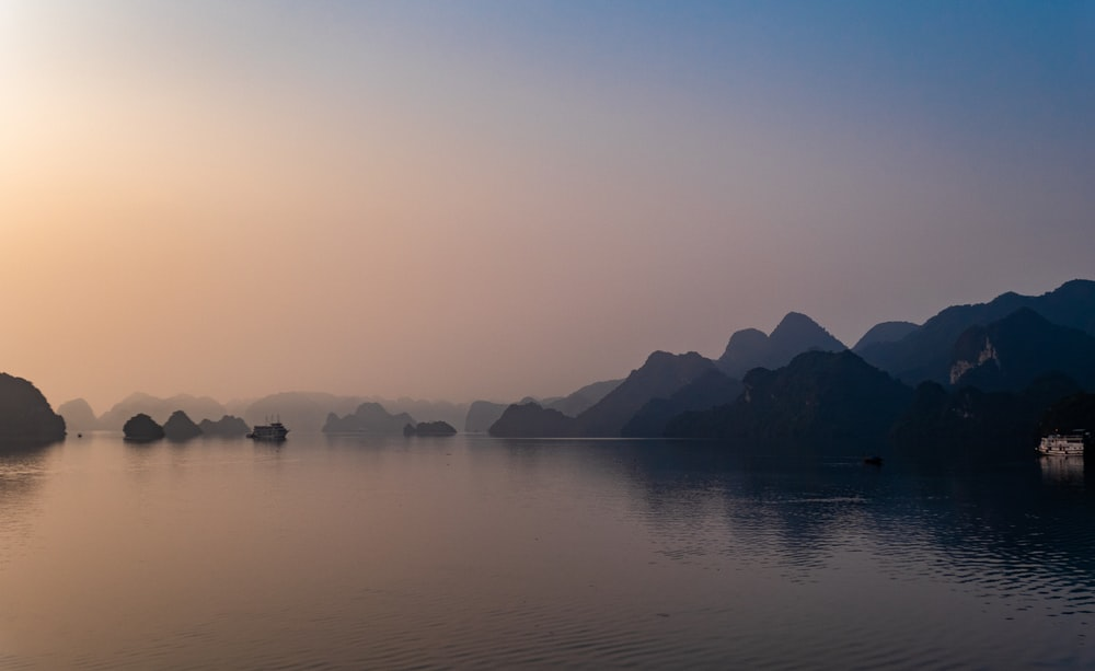 silhouette of mountains near calm body of water