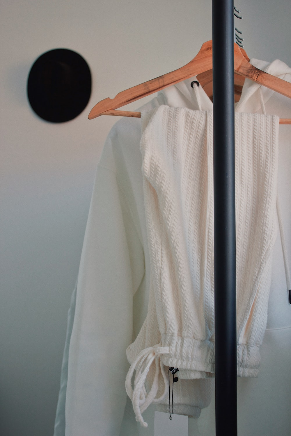 white drawstring jeans and hoodie on hanger