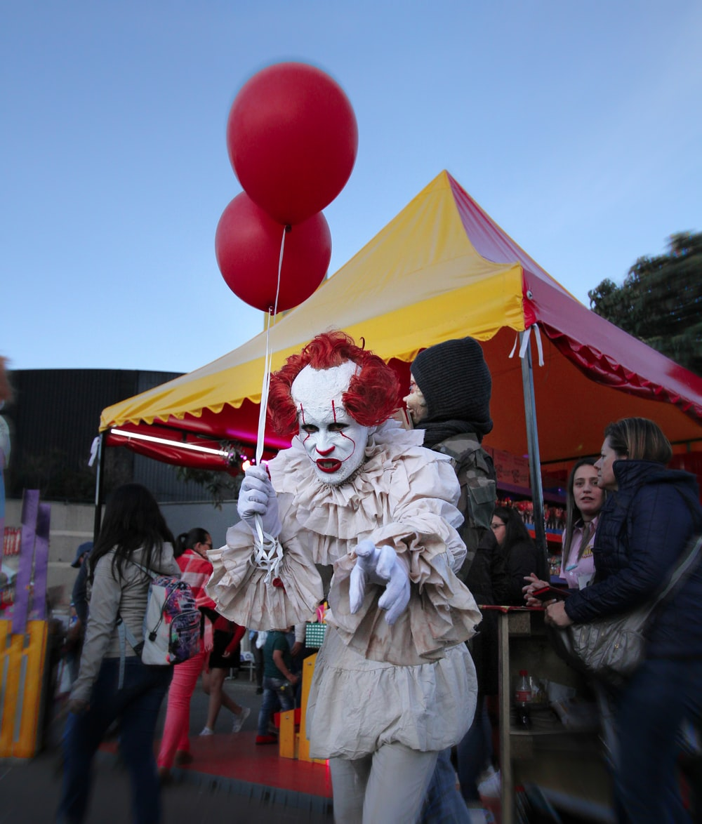 clown holding two red balloons