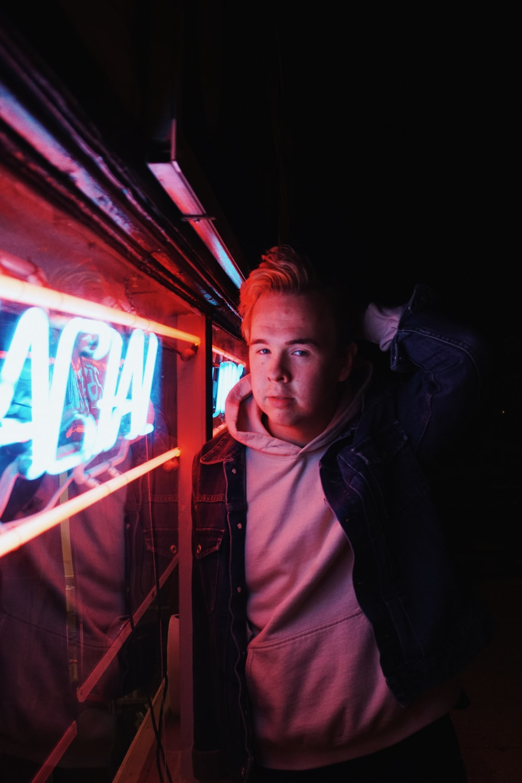 man standing beside neon light signage
