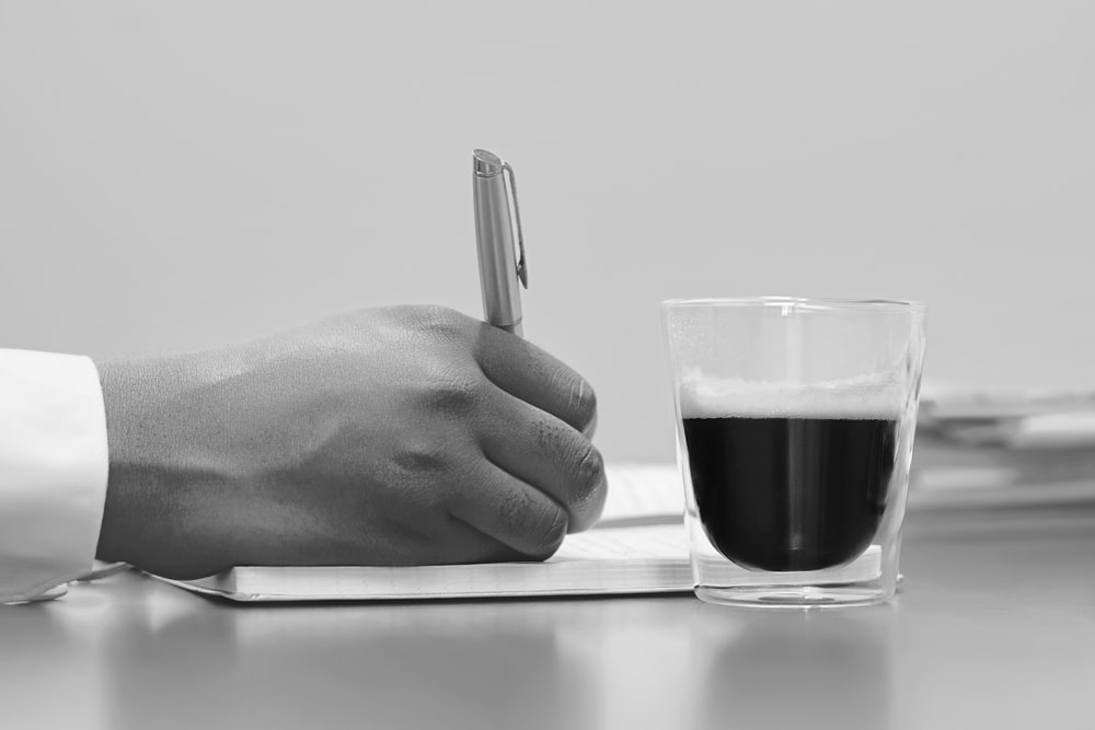 person writing on note book beside filled cup