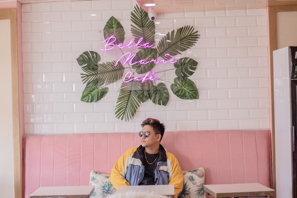 man wearing jacket sitting on pink fabric sofa inside Bellas Marie Cafe