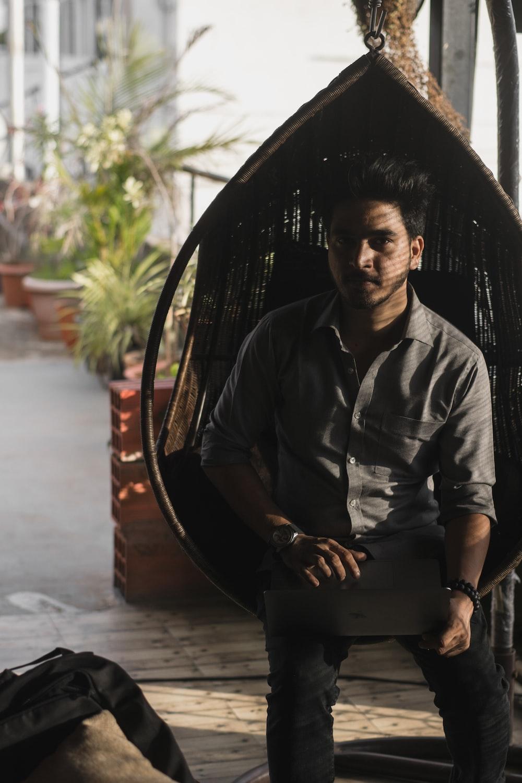 man sitting on brown hanging chair