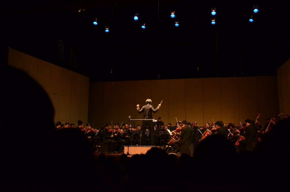 orchestra playing in dim-lit room