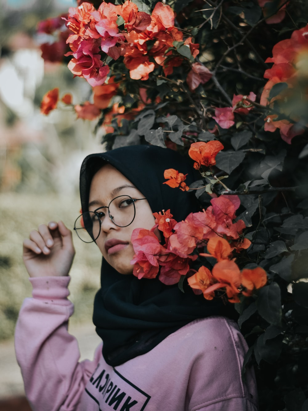 selective focus photography of woman standing beside flower during daytime