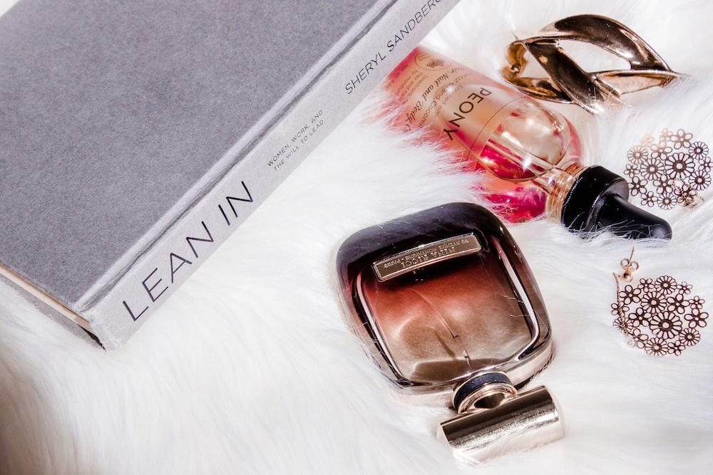 two perfume bottles on white fur textile