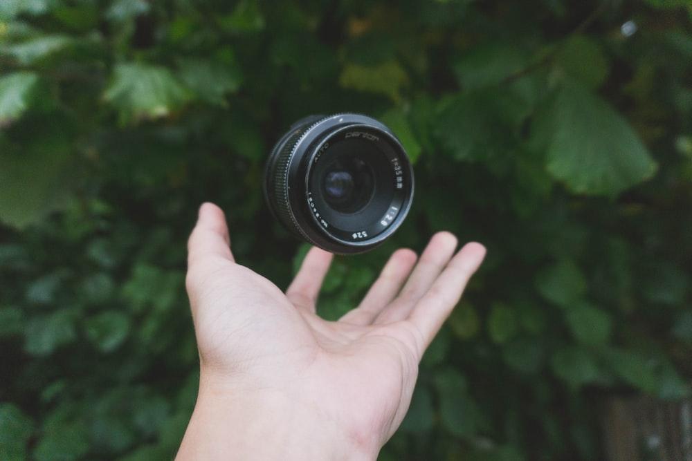 person showing black DSLR camera