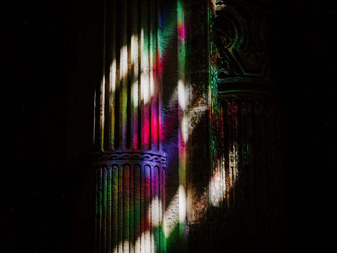 A cast of light through the stained glass of the dark Iglesia del Divino Salvador in Seville.