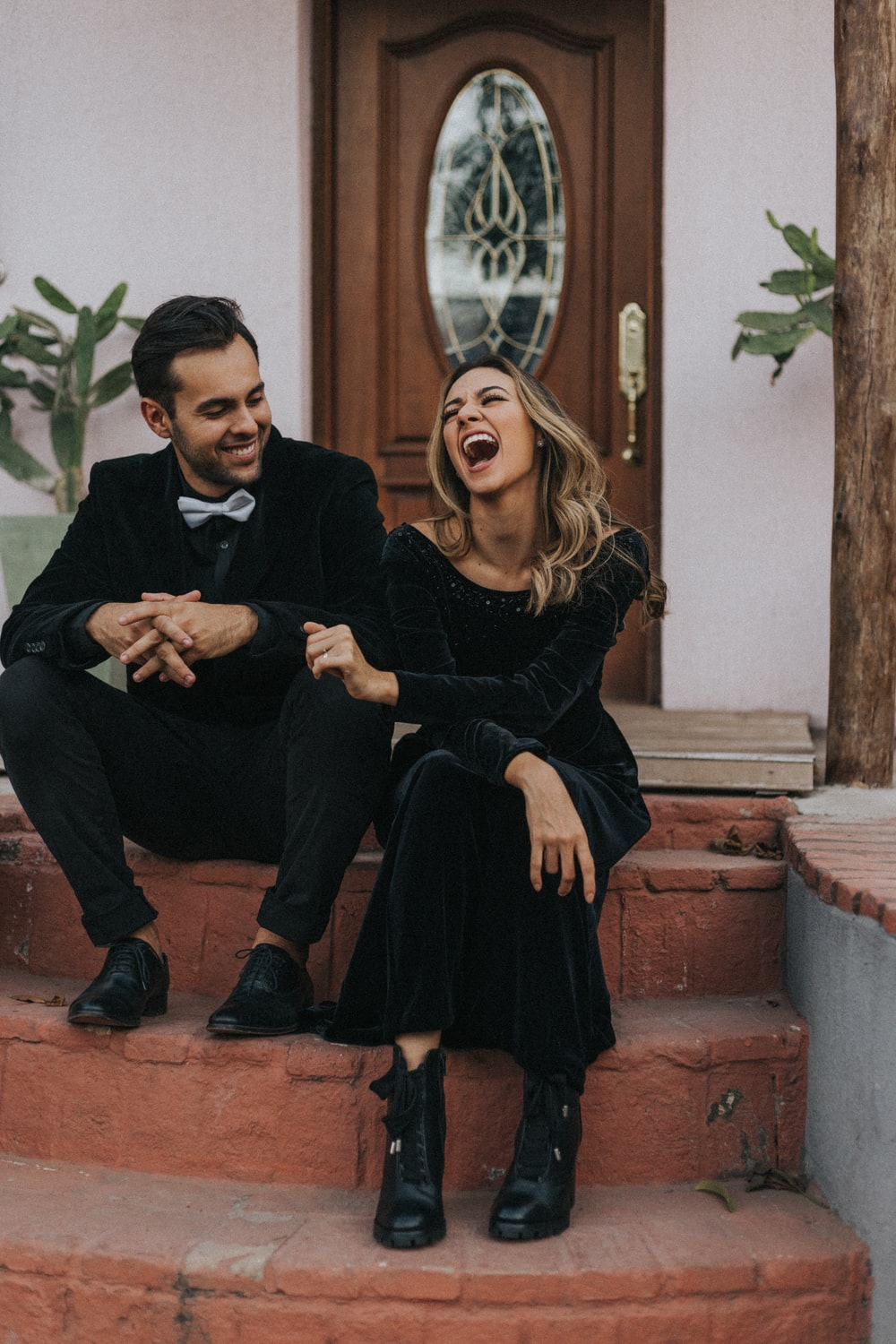 man and woman laughing outside house